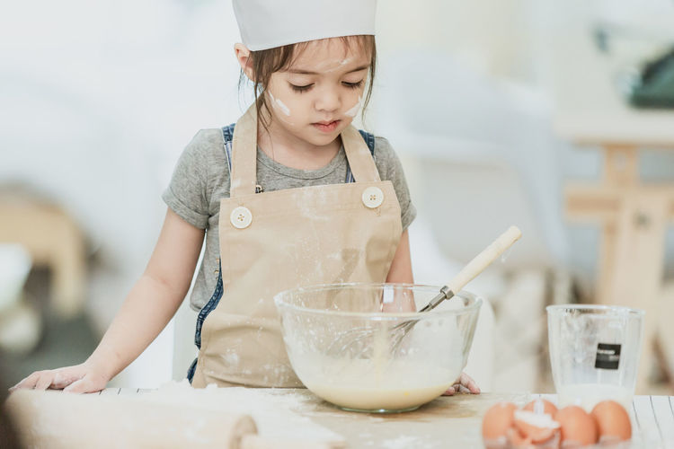 Portrait of girl with ice cream in bowl on table