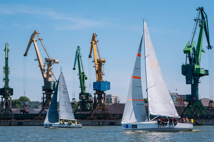 Sailboats in harbor against sky