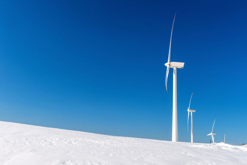 Low angle view windmill on field against sky during winter