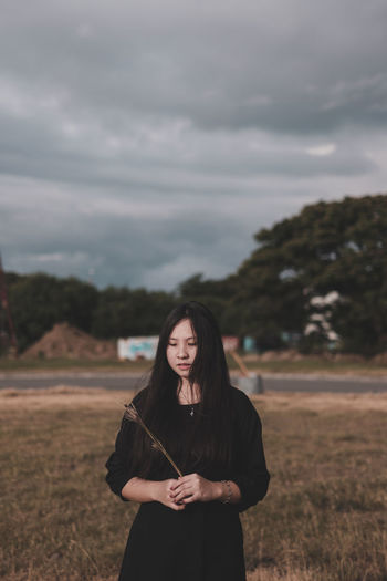Portrait of young woman standing on field against sky