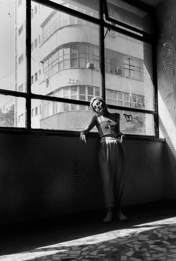 Full length of woman standing against window