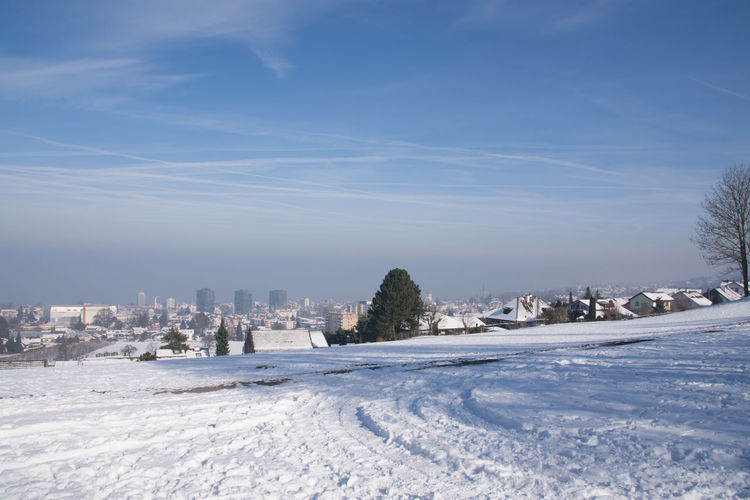 Snow covered land and buildings against sky