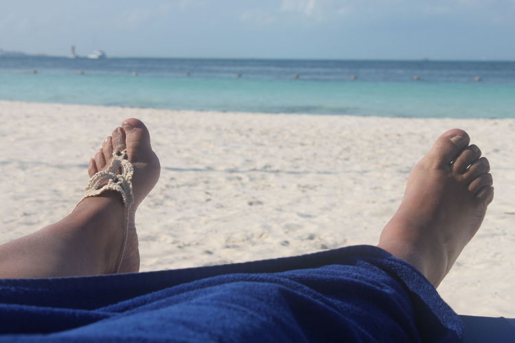 Low section of woman relaxing on beach