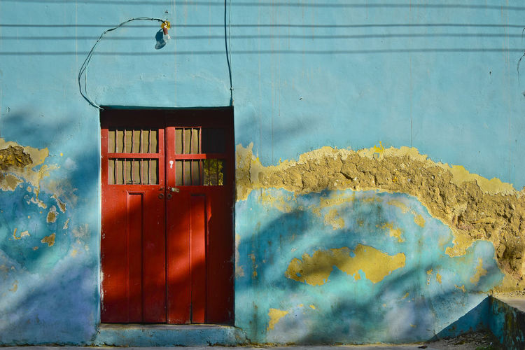 Red door with turquoise wall in a rural town of Yucatan, Mexico Architecture Daytime Red Rural Turquoise Colored Wall Agua Color Day Door Doorway Light And Shadow No People Shadows Wires Yucatan Mexico