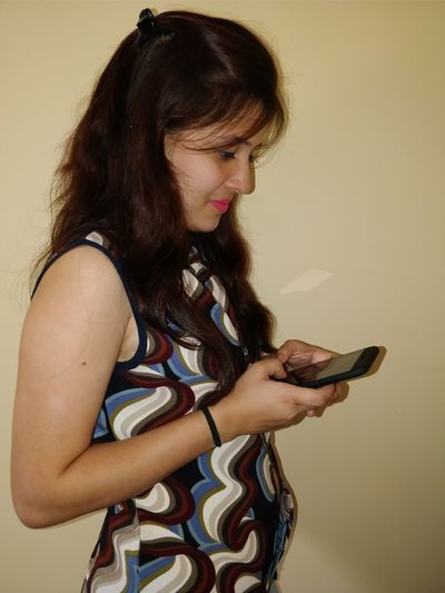 Young woman using mobile phone by wall at home