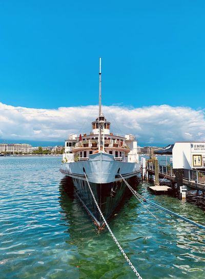 Ship moored on sea against blue sky