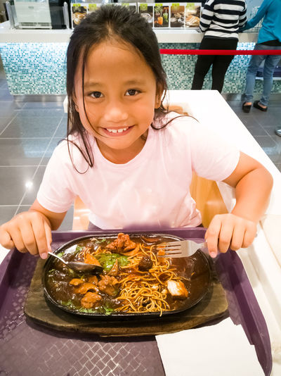 Portrait of smiling girl with food in plate
