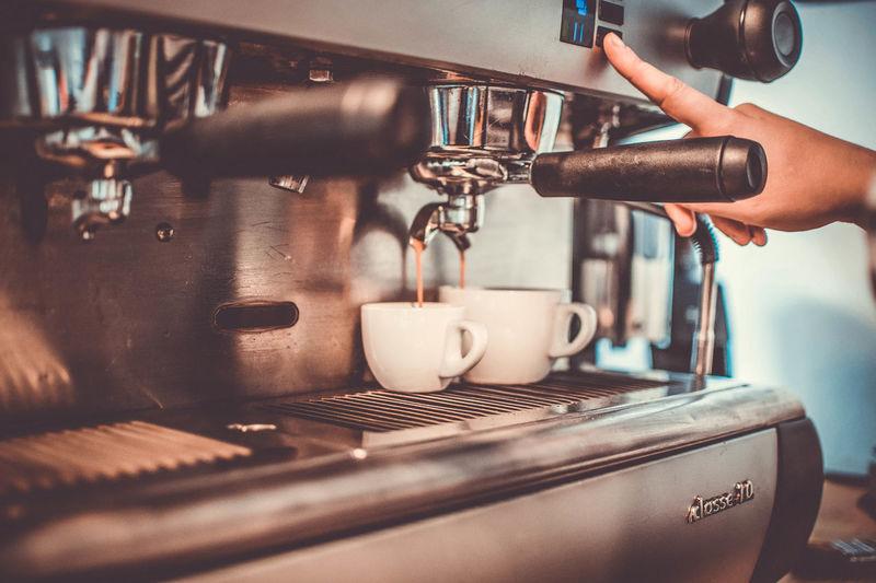 Cropped image of hand pouring coffee in cafe