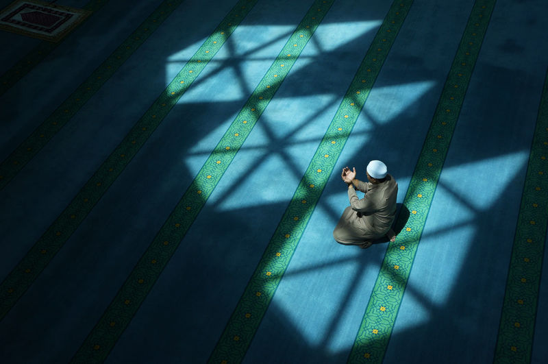 High angle view of man praying in mosque