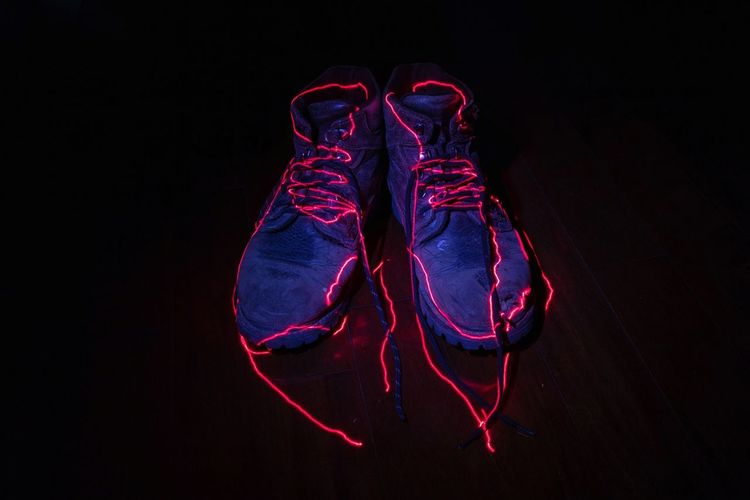 Low section of shoes over black background