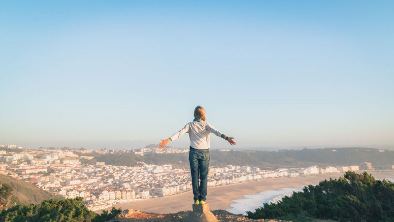 Adventure Blue Sky Clear Sky Cliff Edge Elation Embrace Fly Free Hiking Lanscape Let Go Nature Nazaré  Portugal Scenics Sea And Sky Sky Standing Sunset Town In The Distance Travel Destinations Vacation View Woman