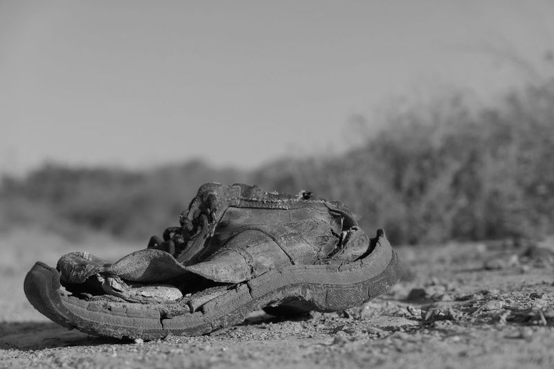 Close-up of abandoned shoes on field