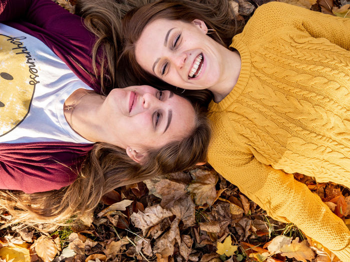 Human Connection Lying Down Happiness Smiling Emotion Young Adult Young Women Women Adult Leisure Activity Lying On Back Hair Portrait Positive Emotion Relaxation High Angle View Togetherness People Cheerful Lifestyles Hairstyle Beautiful Woman Sister Bonding Fall Leaves