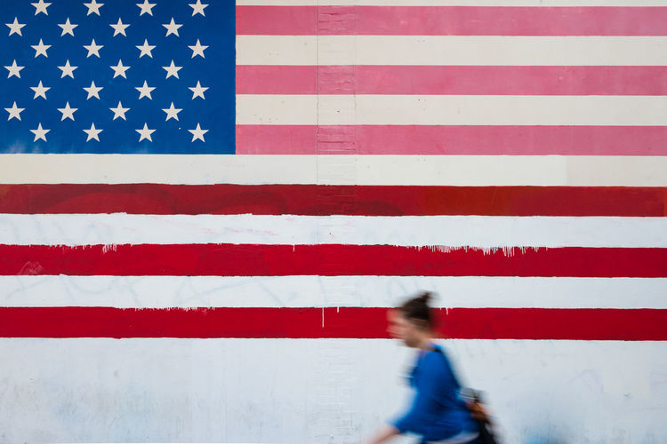 Blurred motion of woman walking by wall with american flag