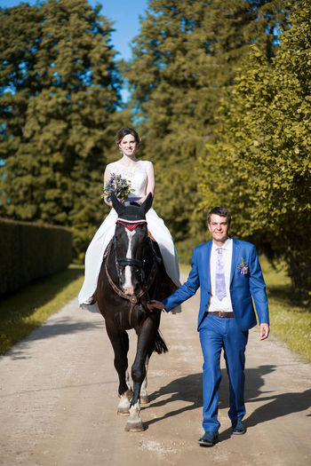 Portrait of bride and groom with horse walking on road