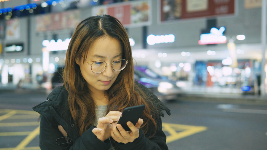 Young Woman Using Smart Phone On Street At Night