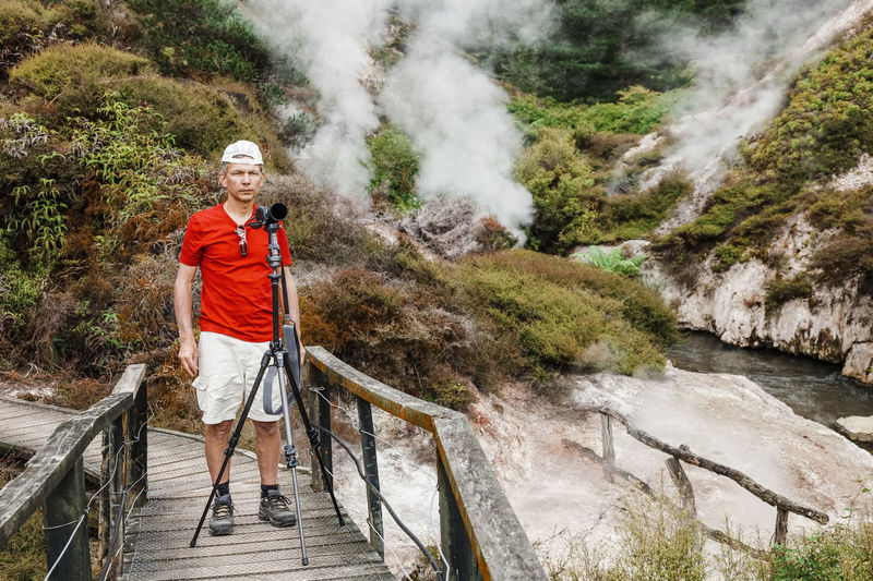 Senior man with camera tripod standing on footbridge by stream