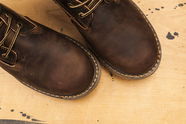 Brown men's boots, on a wooden background Brown Men's Boots, On A Wooden Background