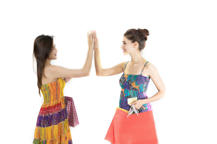 Friends Giving High-Five While Standing Against White Background
