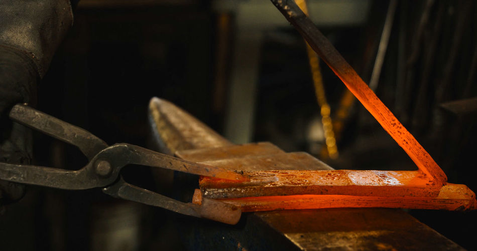 Cropped image of blacksmith working in workshop