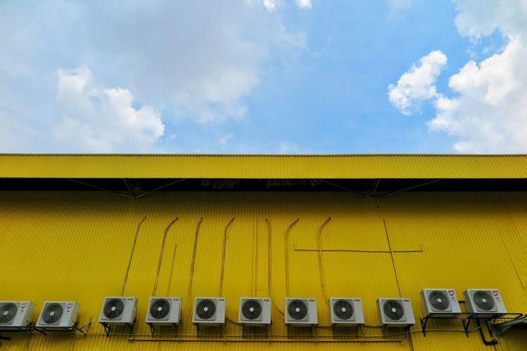 Low Angle View Of Air Conditioners On Yellow Building Against Sky