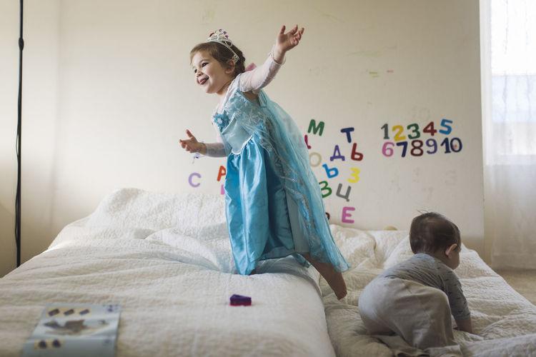 Full length of children on bed at home