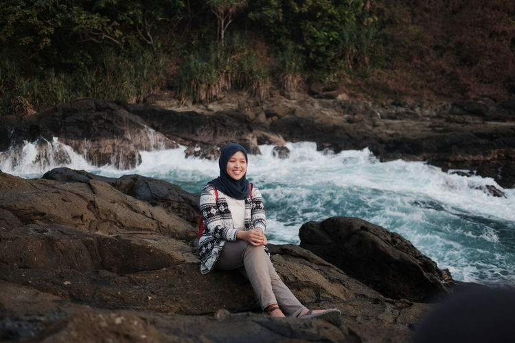 Smiling woman wearing hijab sitting on rock by river