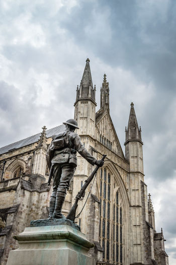 Low Angle View Of Statue By Winchester Cathedral Against Cloudy Sky