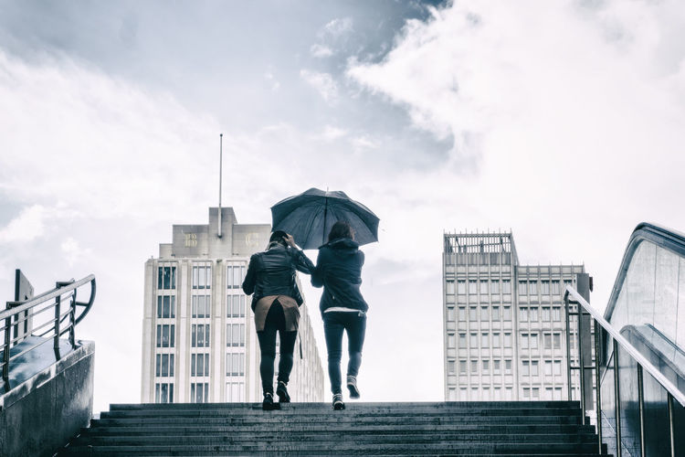 Rear view of women with umbrella at staircase against sky during rainy season