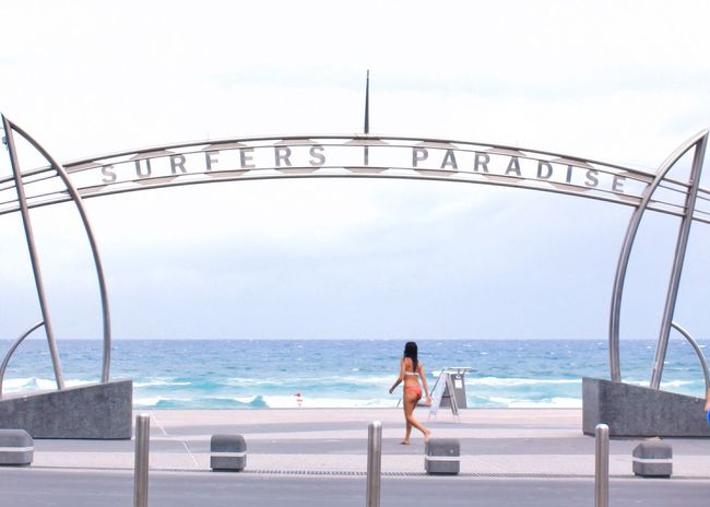 Girl in a bikini walking under the 'Surfers Paradise' sign, with ocean in background ... at Surfers Paradise - Gold Coast, Australia Surfers Paradise Sign Iconic Signage Woman Street Streetphotography Street Photography Beachside People Of The Oceans Ocean Background Australia Gold Coast Australia Gold Coast Summer Summertime Tourism Destination Girl Power The Great Outdoors With Adobe Feel The Journey My Favorite Photo The Essence Of Summer Women Around The World Live For The Story Been There.