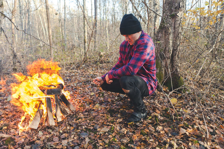 Man roasting food in campfire at forest