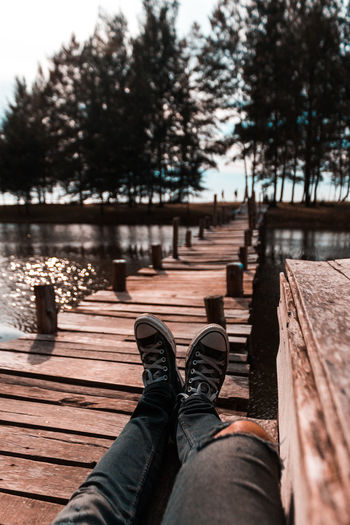 Low section of person relaxing on wooden footbridge
