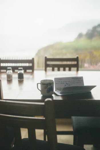 letter writing with coffee by the window Table Seat Chair No People Focus On Foreground Nature Day Absence Outdoors Empty Water Text Communication Still Life Close-up Cup Wood - Material Sky Restaurant Furniture