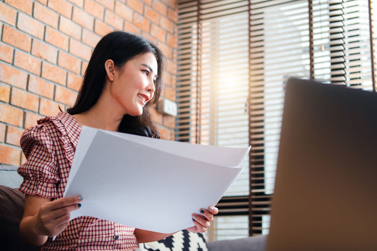 Woman holding a smiling while sitting in front of office