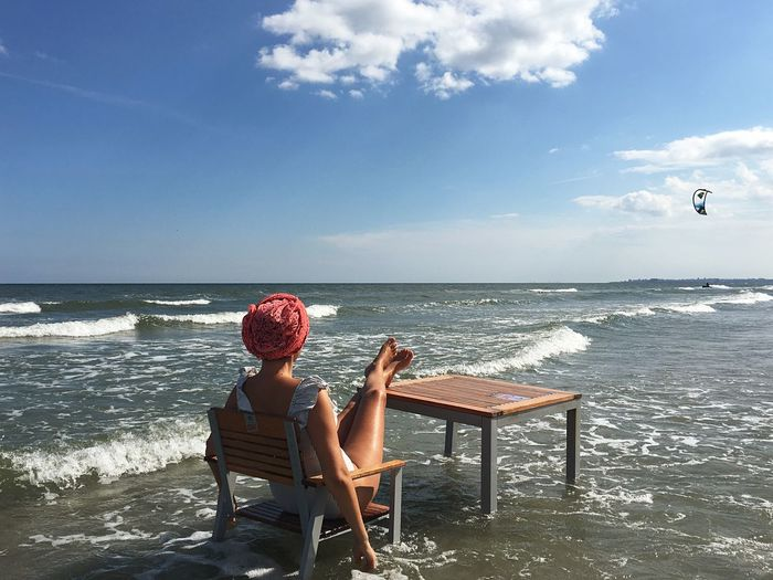 Rear view of woman sitting on chair at beach against sky