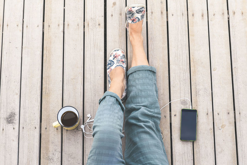 Low section of woman with coffee and smart phone on wooden plank