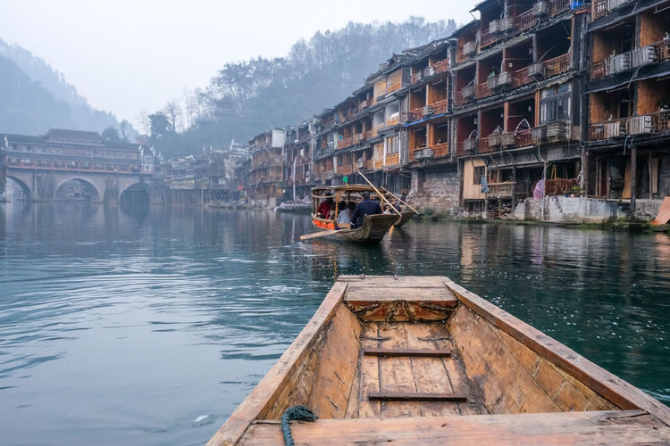 Wooden boat in lake against buildings