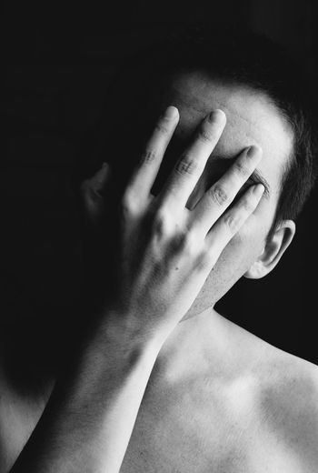Close-Up Of Shirtless Man Covering Face Against Black Background