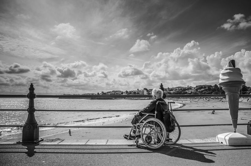 Rear view of man cycling by sea against sky