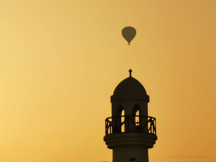 Low angle view of silhouette tower against orange sky
