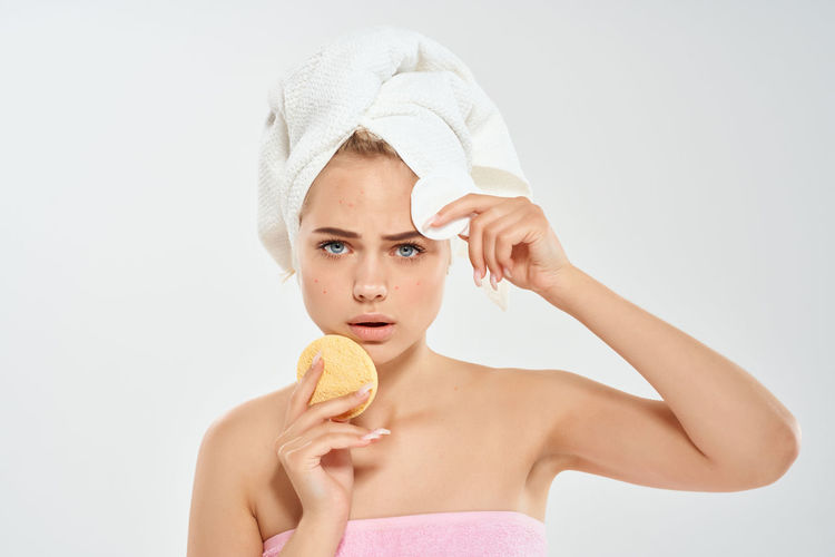 Portrait of young woman holding ice cream against white background