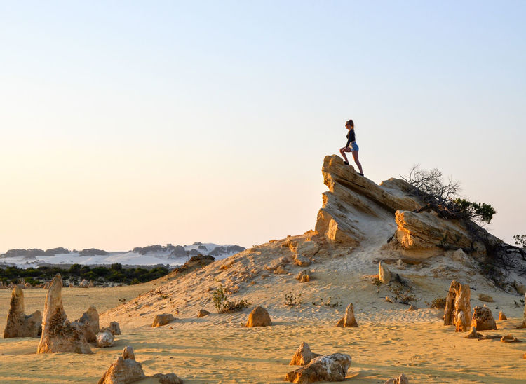 Person climbing the limestone rocks in the Pinnacles Desert at twilight in Western Australia. Adventure Australia Climbing Day Desert Eco Tourism Landscape Limestone Nambung National Park Nature Outdoors People Pinnacles Rock Sand Sand Dune Sky Solitude Travel Travel Destinations Twilight Vacations Western Australia Women Young Adult