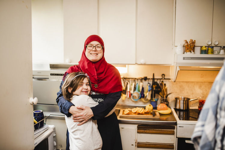 Portrait of happy mother with daughter standing at home