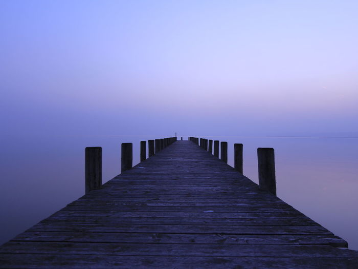 Pier Over Calm Lake Against Sky During Sunset