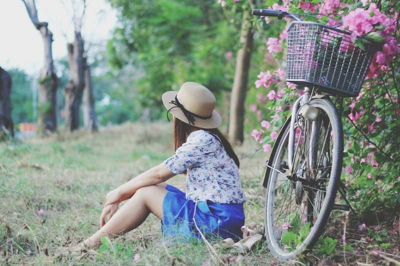 Side view of young woman sitting with bicycle parked at park