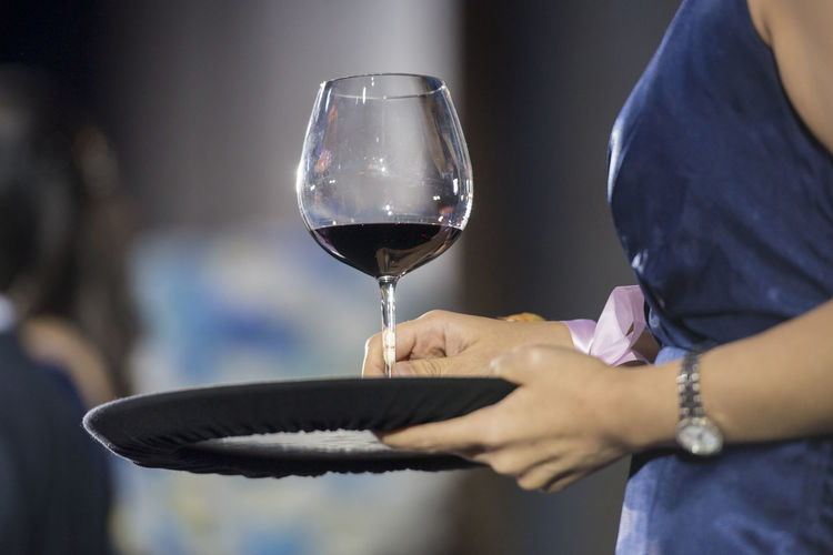 Close-up of woman holding wine glass on table