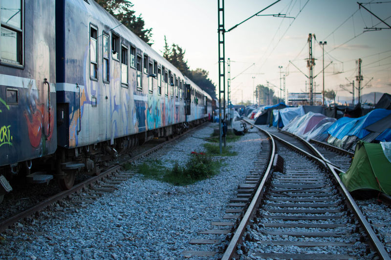 Train on tracks by refugee camp tents