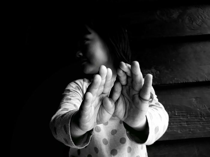 Girl looking away and showing stop gesture while standing against wall at home
