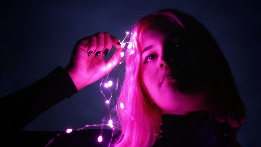 Portrait of young woman with pink hair against black background