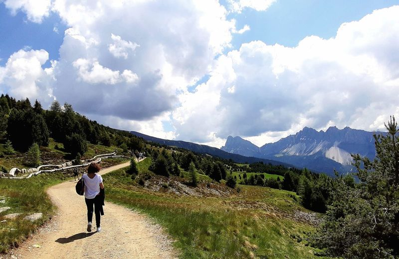 Rear view of woman walking on road by mountain against sky